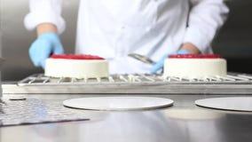 O cozinheiro chefe de pastelaria das mãos prepara um bolo, tampa com crosta de gelo e decora-o com morangos, trabalhos em uma coz video estoque