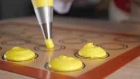 O cozinheiro chefe de pastelaria está cozinhando bolinhos de amêndoa Massa de derramamento na esteira do silicone do estêncil filme