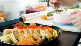 O cozinheiro chefe de sushi decora o sushi ajustado com o caviar de peixes de voo vídeos de arquivo
