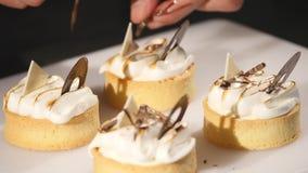 O cozinheiro chefe decora o bolo da sobremesa Close-up dos toques finais O homem entrega o pasteleiro Cair sobre queques do choco filme