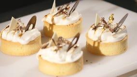 O cozinheiro chefe decora o bolo da sobremesa Close-up dos toques finais O homem entrega o pasteleiro Cair sobre queques do choco vídeos de arquivo
