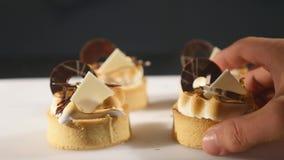 O cozinheiro chefe decora o bolo da sobremesa Close-up dos toques finais O homem entrega o pasteleiro Cair sobre queques do choco video estoque