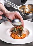 O cozinheiro chefe decora o risotto Imagem de Stock Royalty Free