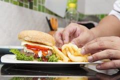 O cozinheiro chefe decorou o Hamburger e os franceses fritados Fotos de Stock
