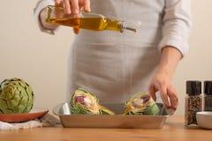 O cozinheiro chefe derrama o azeite e prepara-se para cozer a alcachofra em um fundo claro, o conceito de cozinhar o alimento sab imagens de stock