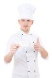 O cozinheiro chefe do homem novo nos polegares uniformes levanta e mostrando a visita vazia Foto de Stock Royalty Free
