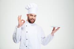 O cozinheiro chefe do homem que mostram o sinal aprovado e vazios plat Fotos de Stock