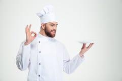 O cozinheiro chefe do homem que mostram o sinal aprovado e vazios plat Imagem de Stock Royalty Free