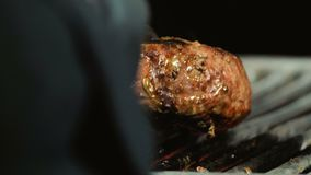 O cozinheiro chefe em luvas pretas e com tenazes de brasa do ferro toma o rissol suculento cozinhado do hamburguer da grade, prat video estoque