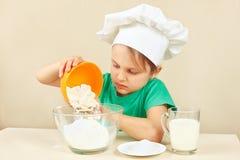 O cozinheiro chefe engraçado pequeno derrama a farinha para o bolo de cozimento imagens de stock royalty free