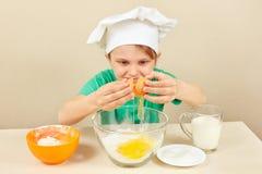 O cozinheiro chefe engraçado pequeno derrama ovos para o bolo de cozimento foto de stock