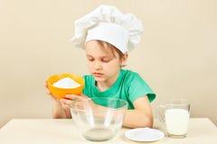 O cozinheiro chefe engraçado pequeno na tabela com ingredientes está indo cozinhar o bolo foto de stock