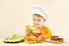 O cozinheiro chefe engraçado pequeno põe a alface sobre o sanduíche fotografia de stock