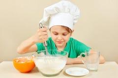 O cozinheiro chefe engraçado pequeno prepara a massa para o bolo de cozimento fotos de stock royalty free