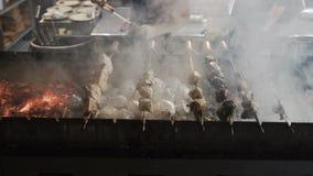 O cozinheiro chefe entrega o cozimento do assado roasted da carne com lotes do fumo No espeto grelhado no espeto do metal vídeos de arquivo