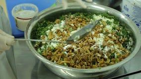 O cozinheiro chefe entrega a mistura e conserva a salada dos cogumelos e de legumes frescos video estoque