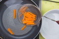 O cozinheiro chefe escalda a cenoura com água quente fotografia de stock royalty free