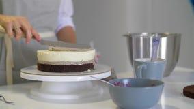 O cozinheiro chefe espreme o creme Cereja sobre o bolo do chocolate Bolo branco coberto com o chocolate e o creme Decoração do bo filme