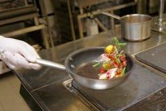 O cozinheiro chefe está agitando o alimento na bandeja Fotografia de Stock