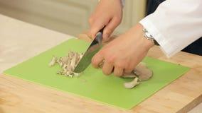 O cozinheiro chefe está cortando cogumelos de Brown em uma placa de corte video estoque