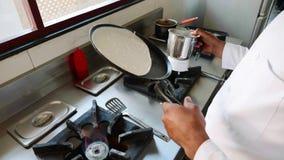 O cozinheiro chefe est? cozinhando panquecas em uma frigideira no restaurante no fog?o de g?s filme