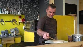 O cozinheiro chefe está cozinhando panquecas grandes finas no café Derrama a massa em uma bandeja quente Fast food do café com um video estoque