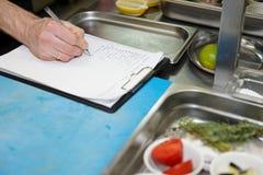 O cozinheiro chefe está criando o prato novo Foto de Stock Royalty Free