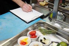 O cozinheiro chefe está criando o prato novo Fotografia de Stock