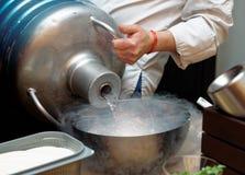 O cozinheiro chefe está derramando o líquido nitroden de uma grande embarcação do vaso Dewar Fotografia de Stock