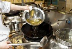 O cozinheiro chefe está derramando o óleo no wok foto de stock royalty free
