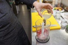 O cozinheiro chefe está derramando o estoque de peixes no misturador imagens de stock royalty free