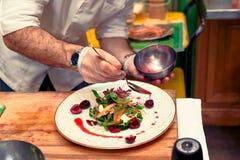 O cozinheiro chefe está derramando o molho no aperitivo vegetal, tonificado imagem de stock