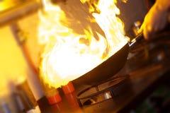 O cozinheiro chefe está fazendo o flambe Fotografia de Stock Royalty Free