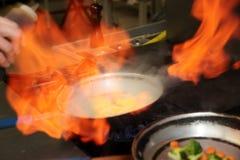 O cozinheiro chefe está fazendo o flambe sauce Fotos de Stock Royalty Free