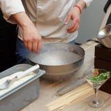 O cozinheiro chefe está imergindo um petisco no nitrogênio líquido Foto de Stock Royalty Free