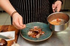 O cozinheiro chefe está servindo o atum fritado com vegetais Imagens de Stock