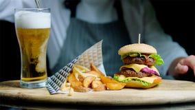 O cozinheiro chefe está servindo o grupo de hamburguer saboroso, de batatas fritas e de cerveja na bandeja de madeira no fundo pr fotos de stock