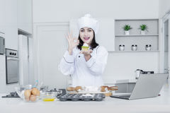 O cozinheiro chefe fêmea com queque mostra o sinal APROVADO Foto de Stock