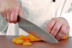 O cozinheiro chefe fêmea corta uma cenoura Foto de Stock