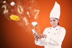 O cozinheiro chefe fêmea está procurando a receita com smartphone foto de stock royalty free