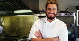 O cozinheiro chefe feliz com braços cruzou a posição na cozinha filme