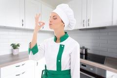 O cozinheiro chefe feliz da jovem mulher que mostra aprovado saboroso assina dentro a cozinha moderna Fotografia de Stock Royalty Free