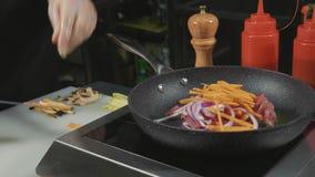 O cozinheiro chefe frita a vários vegetais e carne com manteiga em uma frigideira quente filme