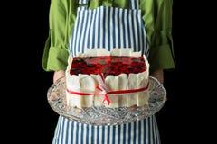 O cozinheiro chefe guarda um bolo da baga em suas mãos Fundo preto Fotografia de Stock Royalty Free