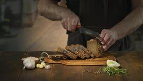 O cozinheiro chefe irreconhecível corta o pão preto em fatias ou em varas para preparar petiscos da cerveja video estoque