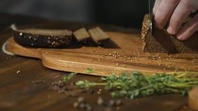 O cozinheiro chefe irreconhecível corta o pão preto em fatias ou em varas para preparar petiscos da cerveja filme