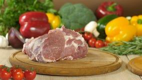 O cozinheiro chefe joga uma parte de carne suculenta crua em uma placa de madeira redonda, nos verdes dos vegetais do fundo, bróc filme