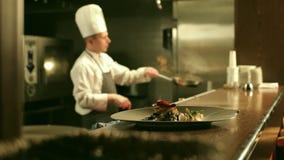 O cozinheiro chefe masculino está cozinhando Flambe na cozinha do restaurante filme