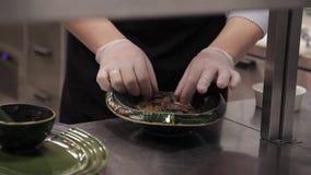 O cozinheiro chefe masculino pôs macarronetes chineses com carne no molho vegetal picante vídeos de arquivo
