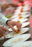 O cozinheiro chefe masculino que decora seu prato, apronta-se para servir fotografia de stock royalty free